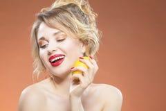 性感的白种人白肤金发的女孩尖酸的黄色柠檬果子 摆在反对橙色背景 免版税库存照片
