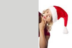 性感的白肤金发的夫人拿着空白广告牌的圣诞老人 免版税图库摄影