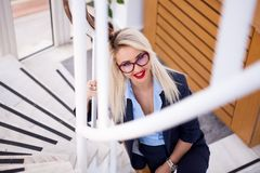 性感的白肤金发的女商人佩带的玻璃 免版税库存图片