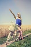性感的白肤金发的女孩在白色自行车附近激发在夏天 免版税库存照片