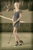 性感的白肤金发的女孩支付高尔夫球,在葡萄酒样式 库存照片