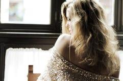 性感的白肤金发的妇女在视窗里 免版税库存照片