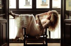 性感的白肤金发的妇女在视窗里 库存照片