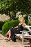 性感的白肤金发的妇女坐长凳时尚 免版税库存照片