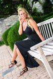 性感的白肤金发的妇女坐长凳时尚 免版税库存图片