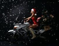 性感的白肤金发的妇女画象圣诞节圣诞老人服装开会乘驾摩托车的 免版税库存图片