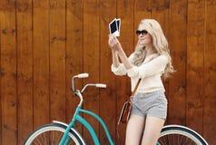 年轻性感的白肤金发的妇女站立在一辆绿色葡萄酒自行车附近的拿着照片和微笑,温暖, tonning 免版税库存图片