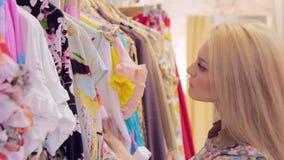 性感的白肤金发的妇女选择在一个挂衣架的衣裳在精品店特写镜头 股票录像