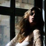 性感的白肤金发的妇女,方式设计,在视窗里 免版税库存图片