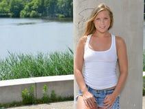 性感的白肤金发的妇女-白色坦克和斜纹布短裤 免版税库存照片