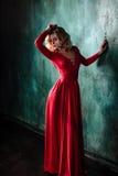 年轻性感的白肤金发的妇女画象一件红色礼服的 图库摄影