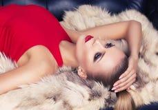性感的白肤金发的妇女画象红色礼服的有皮大衣的 免版税库存照片