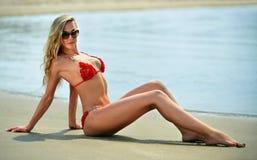 性感的白肤金发的比基尼泳装模型,放置在海洋海滩 免版税库存图片