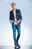 性感的白肤金发的男孩佩带的牛仔裤和皮夹克,当时 免版税库存照片