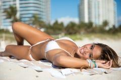 性感的白色比基尼泳装的适合亚裔妇女在海滩摆在说谎 库存照片