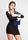 性感的秘书,画象戴眼镜的美丽的深色的企业夫人和佩带在细条纹衣服,拿着一块板材 免版税库存图片