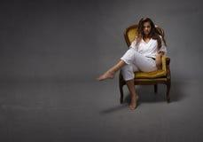 性感的空手道女孩坐沙发 免版税库存照片