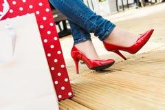 性感的红色高跟鞋的可爱的年轻女性享受断裂的在成功的购物以后 免版税库存照片