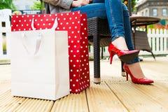 性感的红色高跟鞋的可爱的年轻女性享受断裂的在succesfull购物以后 库存图片