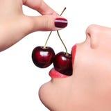 性感的红色嘴唇用被隔绝的樱桃 免版税库存照片