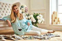 性感的美丽的白肤金发的妇女坐地板神色家庭册页 免版税库存照片