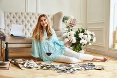 性感的美丽的白肤金发的妇女坐地板神色家庭册页 免版税库存图片