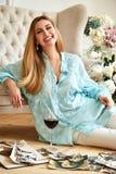 性感的美丽的白肤金发的妇女坐地板神色家庭册页 免版税图库摄影