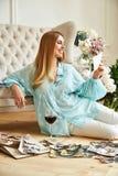 性感的美丽的白肤金发的妇女坐地板神色家庭册页 图库摄影