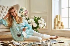 性感的美丽的白肤金发的妇女坐地板神色家庭册页 库存照片