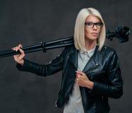性感的聪明的白肤金发的女性摄影师拿着与三脚架的一台专业照相机,摆在演播室 库存图片