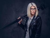 性感的聪明的白肤金发的女性摄影师拿着与三脚架的一台专业照相机,摆在演播室 图库摄影
