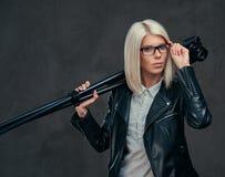 性感的聪明的白肤金发的女性摄影师拿着与三脚架的一台专业照相机,摆在演播室 免版税库存图片