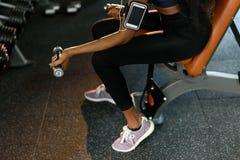 性感的解决与哑铃的健身非裔美国人的妇女的特写镜头手在健身房和听音乐  免版税库存照片