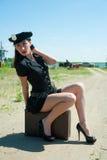 性感的警察妇女坐老手提箱 免版税图库摄影