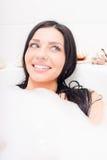 性感的诱人的年轻深色的蓝眼睛妇女说谎的放松在与泡沫愉快微笑的浴&看在旁边特写镜头画象 免版税库存图片