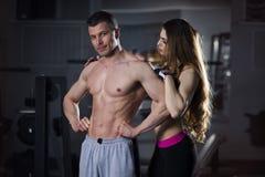 年轻性感的运动男人和妇女在健身以后行使,完善的强健的身体 免版税库存照片