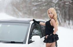 性感的金发碧眼的女人在一辆白色汽车的轮子后在雪的坐 库存照片