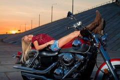 年轻性感的金发碧眼的女人在她的摩托车说谎 免版税库存照片