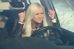 汽车的恼怒的金发碧眼的女人 库存照片