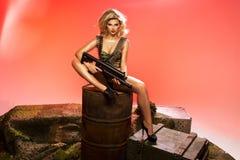 性感的金发碧眼的女人画象有枪的 库存图片