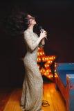 性感的闪烁长的礼服的歌手妇女在与百老汇星的阶段在背景 r 免版税图库摄影
