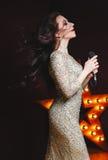 性感的闪烁长的礼服的歌手妇女在与百老汇星的阶段在背景 r 库存图片