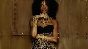 性感的非裔美国人的女性模型豪华画象与摆在织地不很细的照相机的光滑的金黄构成的 库存照片