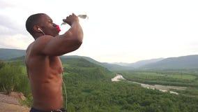 性感的非裔美国人的肌肉在体育训练以后的人饮用水侧视图室外 惊人的绿色 股票录像