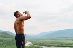 性感的非裔美国人的肌肉在体育训练以后的人饮用水 惊人的绿色山风景  免版税图库摄影