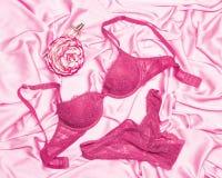 性感的鞋带女用贴身内衣裤设置了与香水和花在桃红色丝绸shee 免版税库存照片