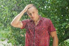 性感的年轻人湿在雨中 库存照片