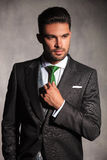 性感的年轻人画象改正他的无尾礼服的领带 免版税库存照片