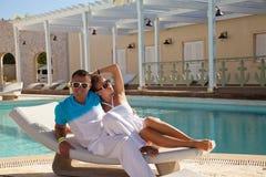 性感的年轻在海滩床上的夫妇松弛近的水池 免版税库存照片