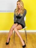 性感的年轻女商人坐在一件短的迷你礼服的一把椅子 库存图片